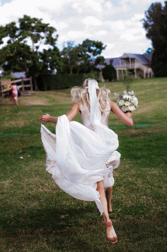 Bride running free, hair wild and barefoot photographed in a natural documentary way